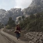 A villager run as Mount Sinabung erupt at Sigarang-Garang village in Karo district